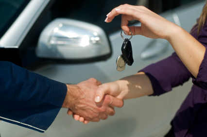 Man and woman shaking hands while handing over car keys