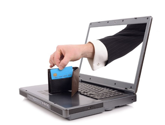 Hand reaching in to lift your credit card information off your laptop.