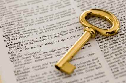Old-fashioned gold key on top of dictionary opened to the word KEYWORD